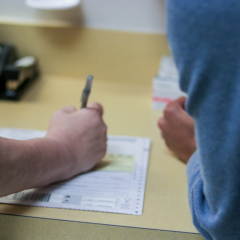 Close up of a student health staff member filling out a form.
